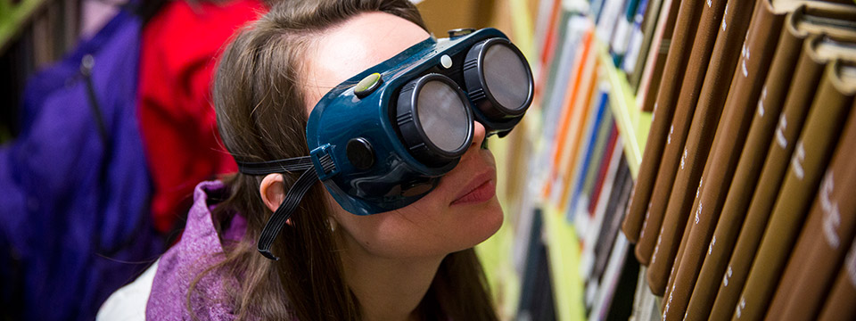Occupational Studies student wears goggles that simulate visual impairment while finding a library book.