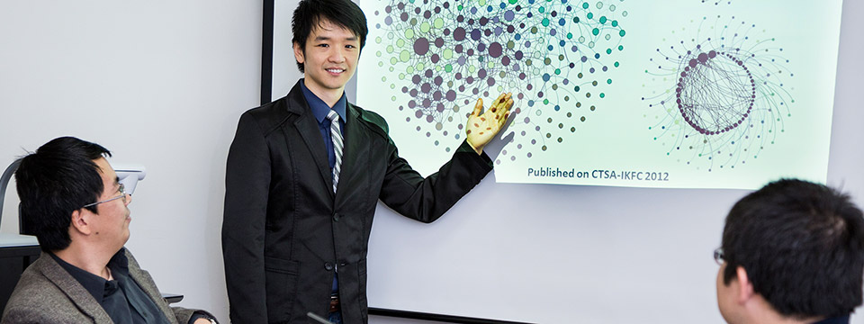Assistant Professor Jake Luo, points to a PowerPoint slide on a screen that shows the relationship analysis of UWM and other healthcare institutions.