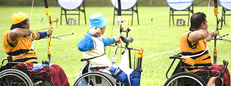 Three men in wheelchairs participate in the adaptive sport of archery.