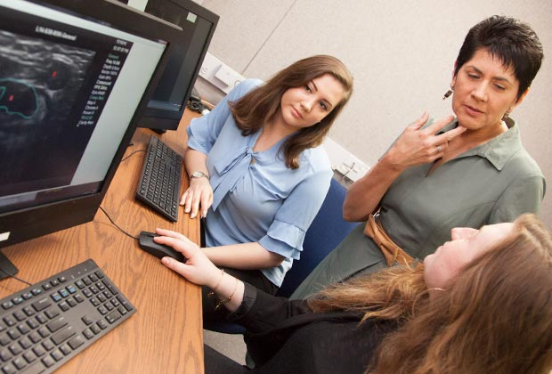Graduate student clinicians work with client with cochlear implants.