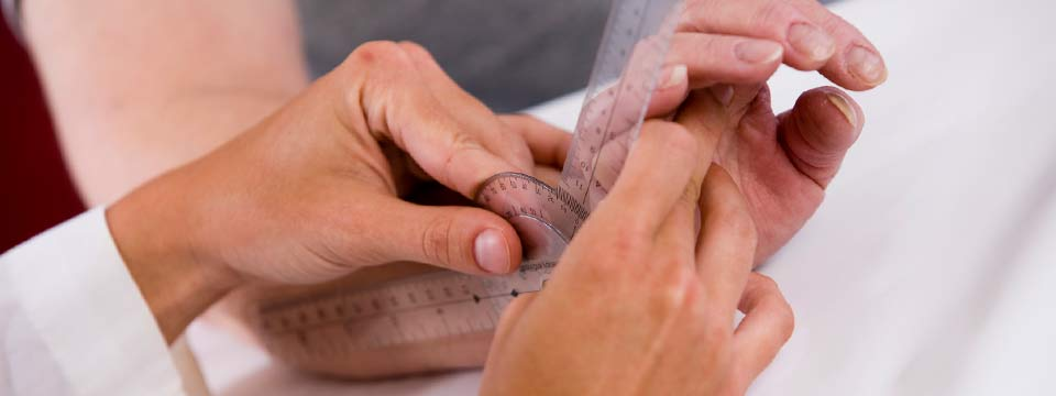 Close-up of a clinician measuring the angle of a patient's wrist flexibility.
