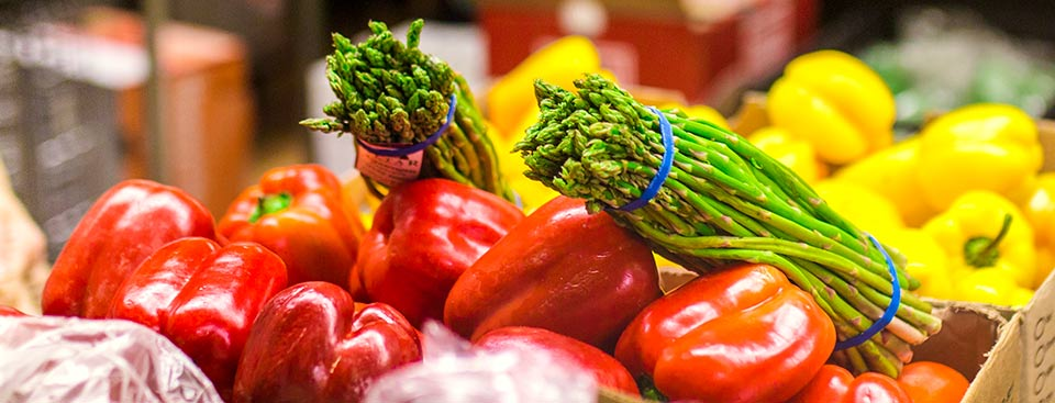 Close up photo of asparagus, and red and yellow peppers.