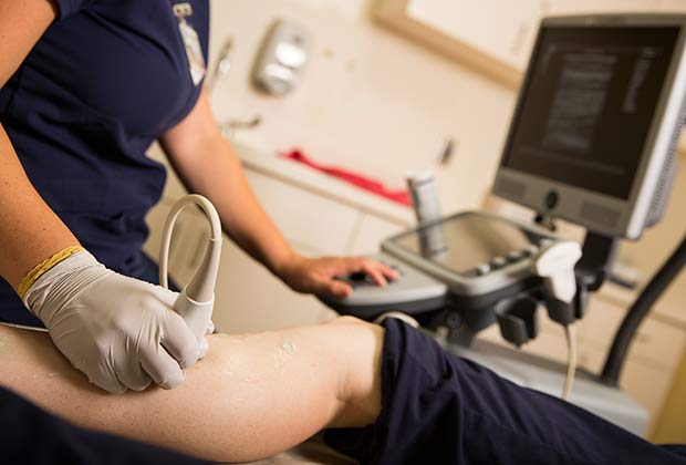 Sonographer uses a linear transducer to perform an ultrasound of a person's leg.