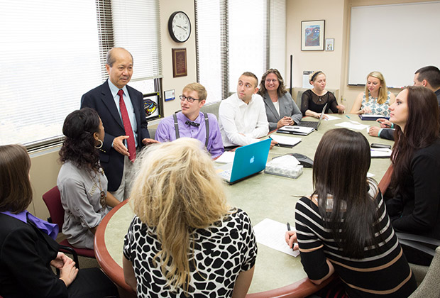Associate Professor Hanh Trinh, PhD, presents Health Care Administration topics to a group of interested undergraduate students sitting around a table.