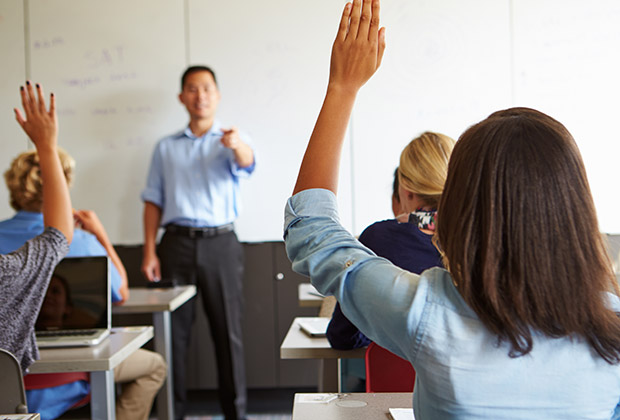 Students raise their hands to answer a question from the instructor at the front of the room.