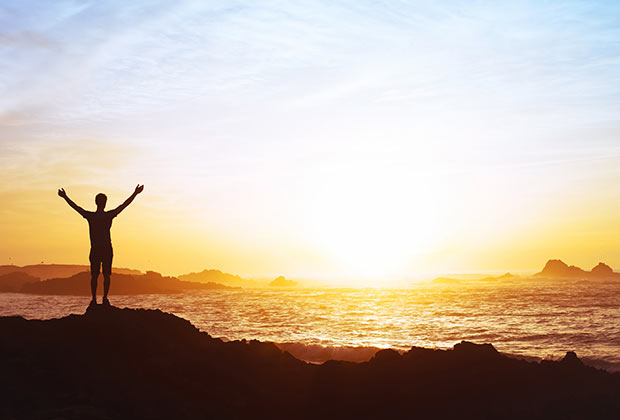 Silhouette of a man holding his arms in the air while watching a sunset over the ocean.