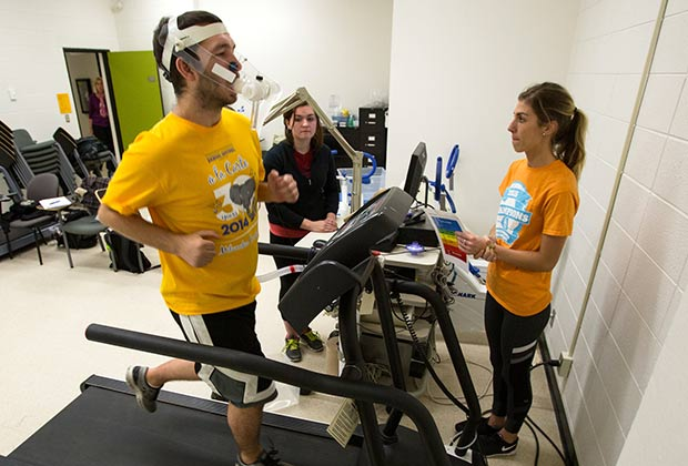 Male student on treadmill with two female students monitoring.
