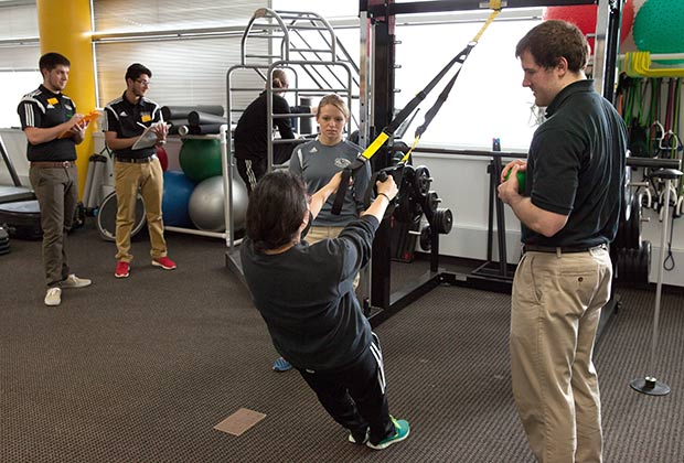 Athletic training students monitoring an exercise routine.