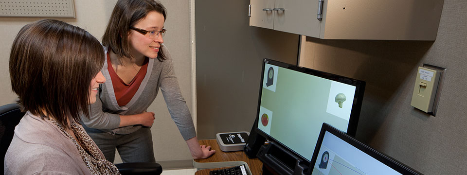 Aphasia Laboratory director, Sabine Heuer, observes as a test subject performs computer mouse movements on two monitors.