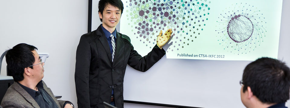 BioDLP Center Director, Jake Luo, points to a PowerPoint slide on a screen that shows the relationship analysis of UWM and other healthcare institutions.
