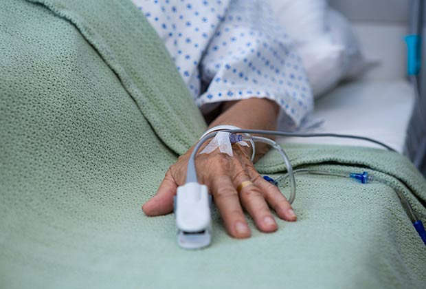 Old woman's hand on a hospital bed with an IV and heart rate monitor on her finger.