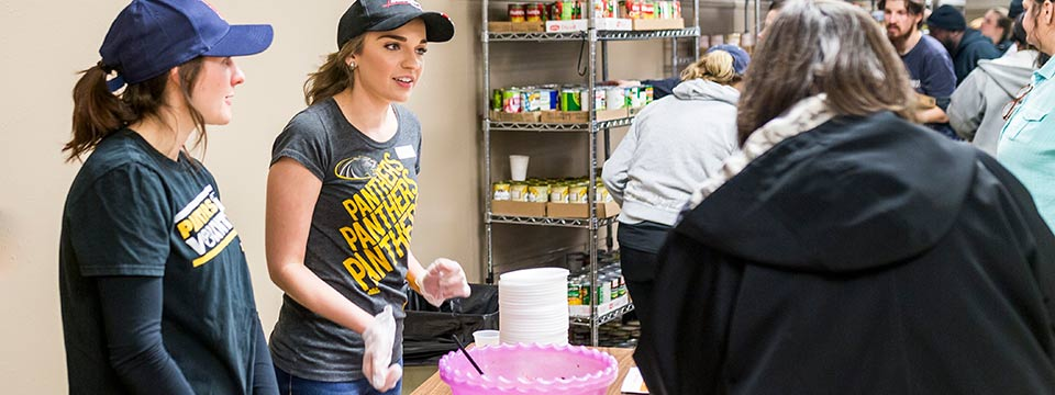 Cassie Ewig (left) and recent graduate Lisa Hren answer questions and pass out samples of their black bean dish. Hren coordinated the demos as part of her internship at the Riverwest Food Pantry. (UWM Photo/Elora Hennessey)