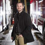 David Cornell poses between two firetrucks parked in a firestation.