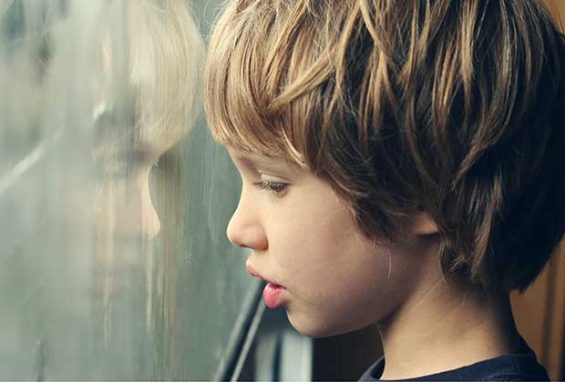 A young boy looking out a window.