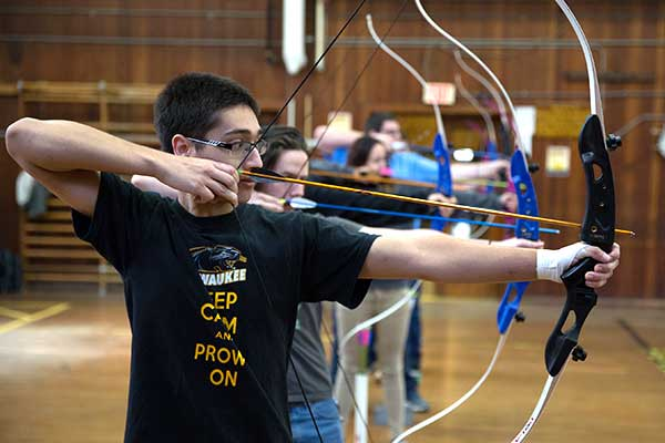 Archery students lined up shooting bow and arrows.