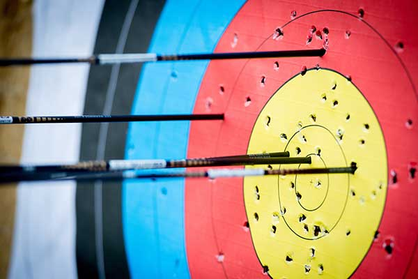 Close up of arrows in a colorful target.