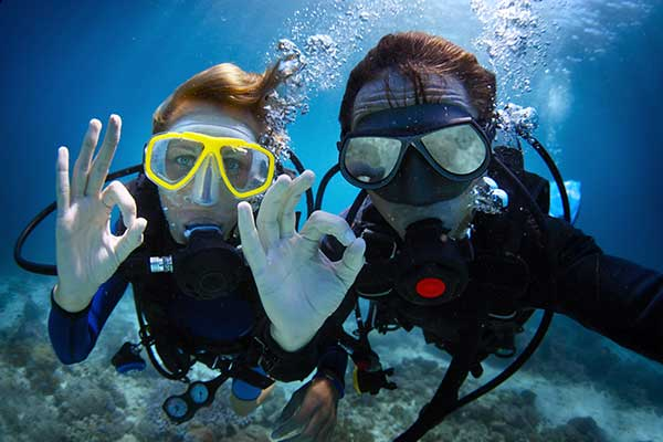 Underwater shot of a young couple diving with scuba in a tropical sea and showing ok signal.