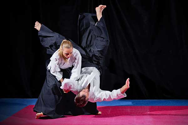 Fight between two aikido fighters on black,