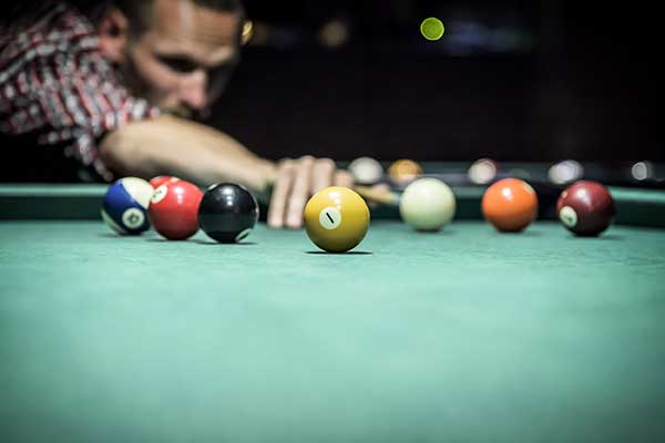 Billiard player ready to strike the ball.