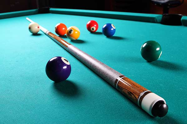 Billiard table with balls and cue.