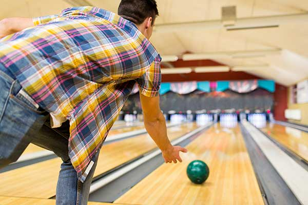 Young man throwing ball to alley in bowling alley.