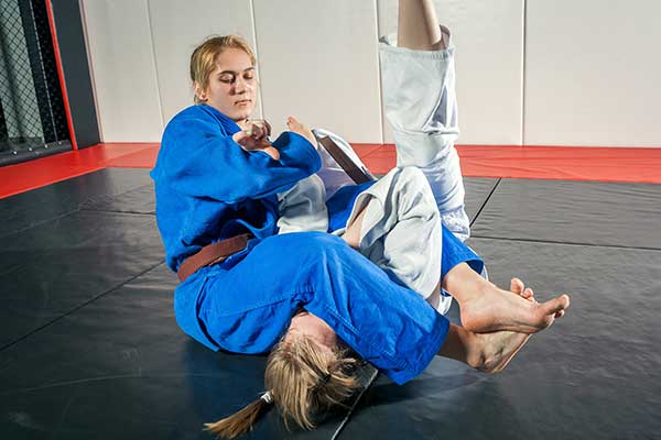 Jiu Jitsu takedown with leg over opponent neck.