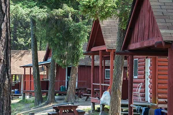 Row of log cabins at a in a wooded area.
