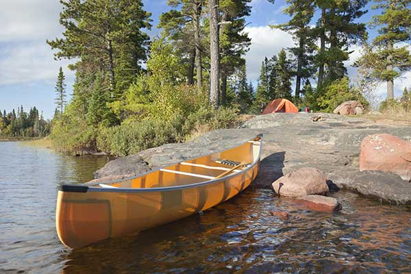 Campsite and canoe on rocky shore of lake.