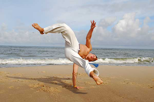Capoeira dancer on the beach.