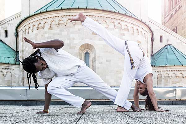 Two young people doing partnership capoeira.