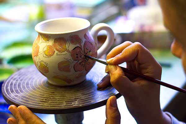 Young man painting a cup.