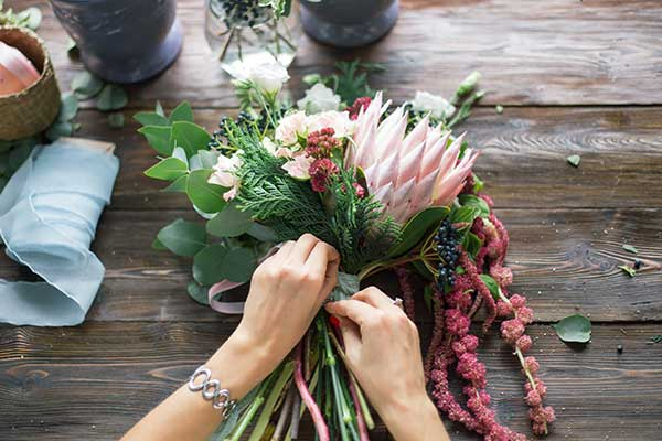 Hand tying a ribbon on a bouquet of flowers.