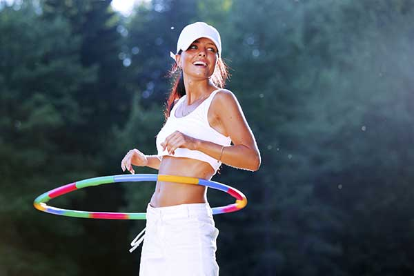 A woman rotates hula hoop on nature background.
