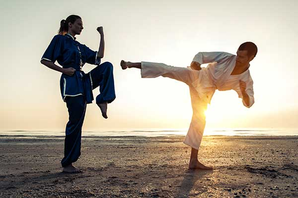 Couple training in martial arts on the beach.