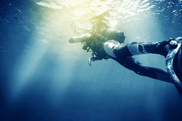 Diver underwater with sunlight breaching surface.