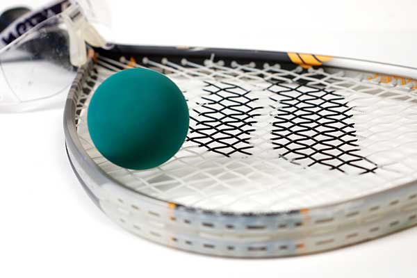 Racquet with ball on top, googles in background.