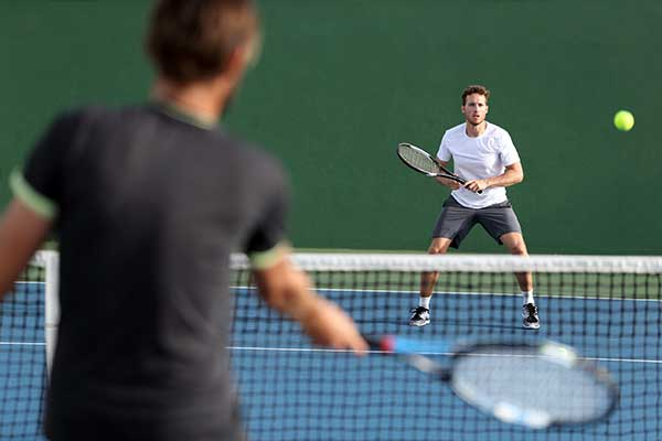 Men sport athletes players playing tennis match together. Two professional tennis players hitting ball on hard outdoor court during game.