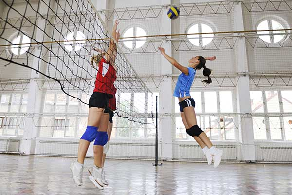 Women playing volleyball indoor game.