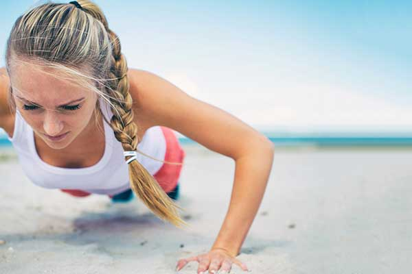 Woman does push-ups on the beach.