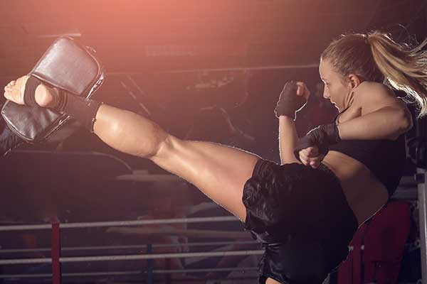 Woman doing back leg high kick during kickboxing exercise.