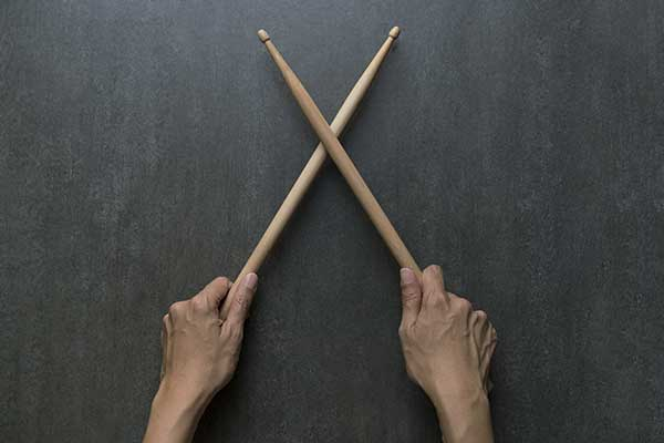 Hands holding drum sticks on black table background.