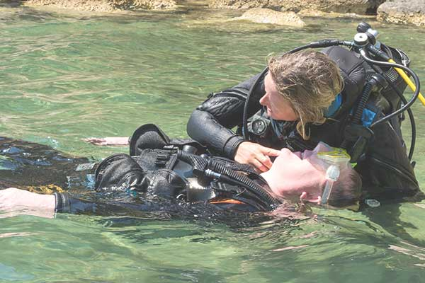 Diver checks casualty for breathing during a rescue practice.