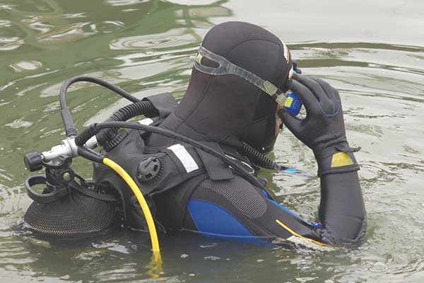 Scuba diver in wet suit entering the cold water.