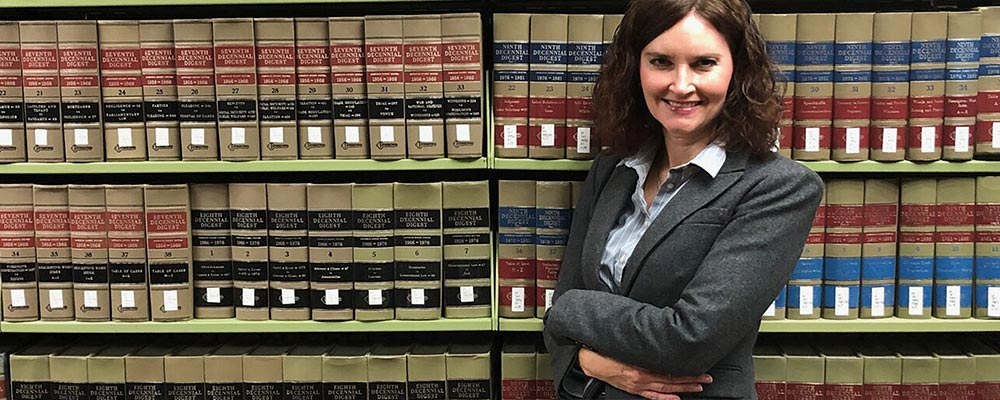 Clinical Assistant Professor Barbara Zabawa, JD, MPH, stands in front of a row of law books in a library.
