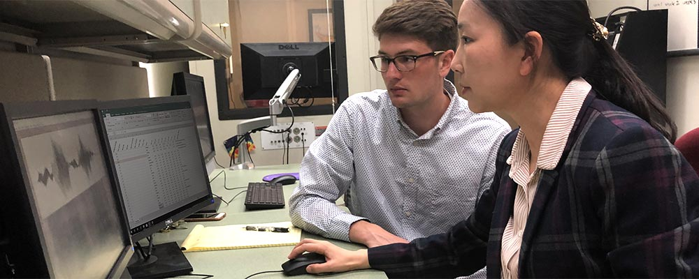 A student from the Department of Communication Sciences and Disorders analyze audio data with Assistant Professor Jing Yang, PhD