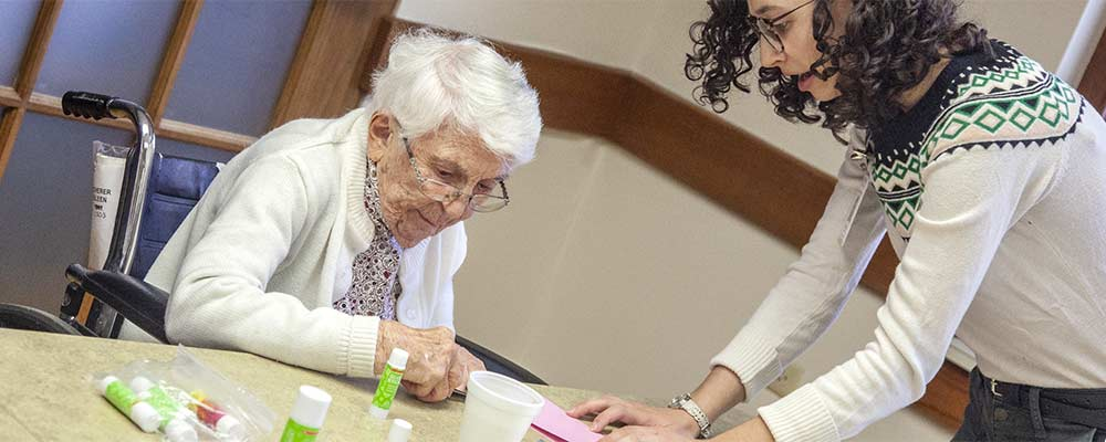 Luther Manor resident Eileen Scherer (left) and Danielle Hobach (right) creating greeting cards.