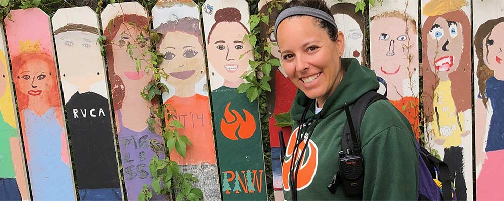 Elizabeth Robbin in front of a fence with children painted on it