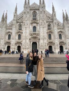 Three student physical therapists in front of a church in Milan.