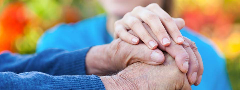 Older adult man's hands resting on the top of a wooden cane. Caregiver's hand gently rests atop his hands.