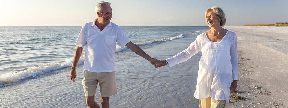 Senior couple takes a walk on the beach hand-in-hand